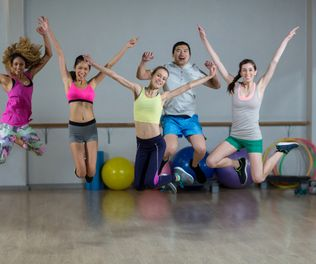 Portrait of group of fitness team jumping in fitness studio